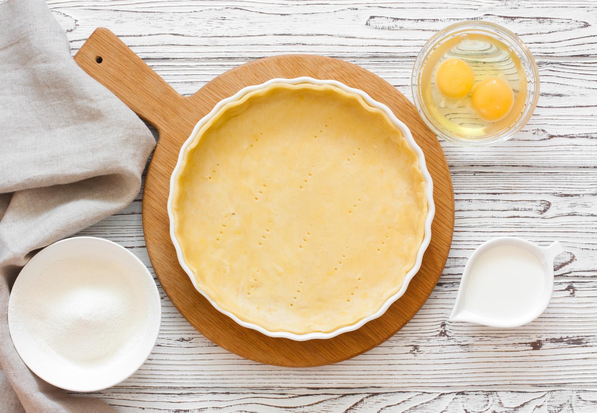 foto de massa sablée em uma travessa, com ovos, leite e farinha