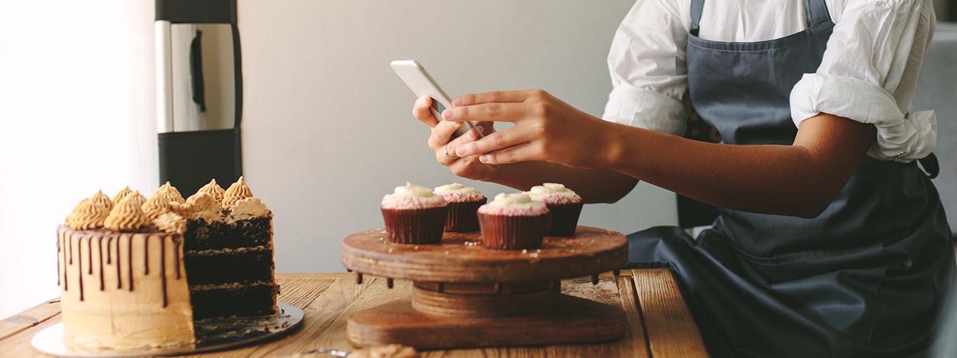 pessoa tirando foto de um bolo confeitado de chocolate para vender na internet