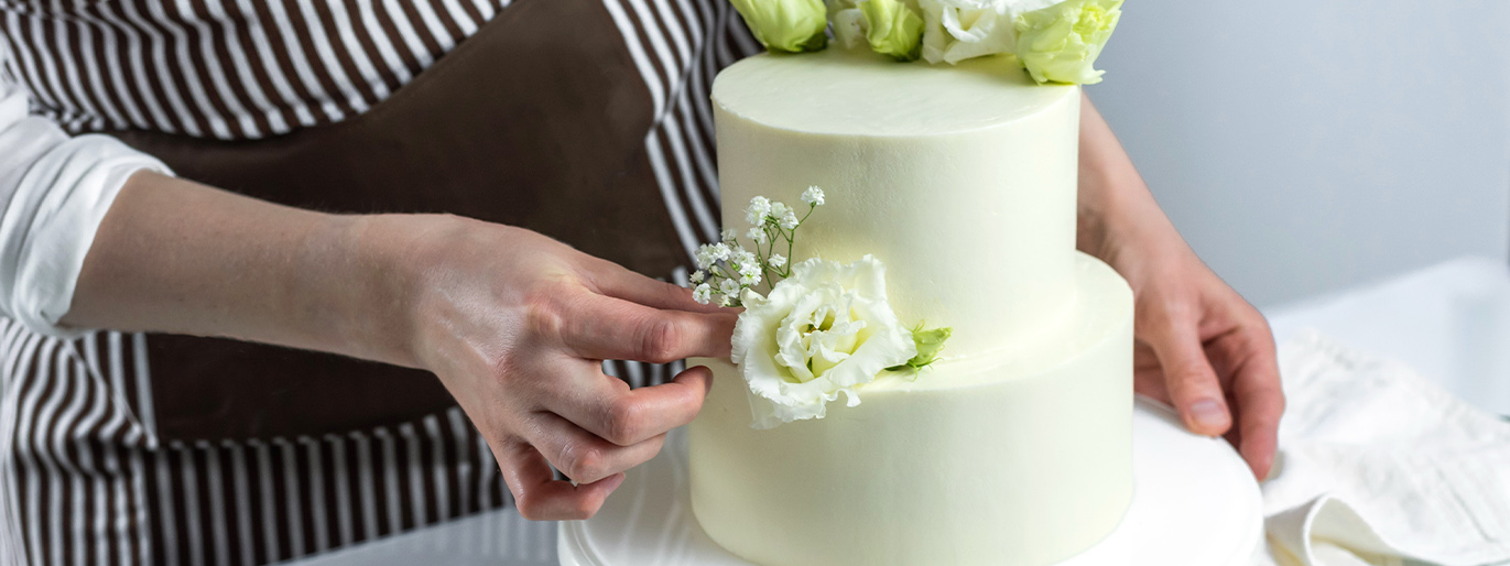 pessoa colocando uma flor de decoração em um bolo branco